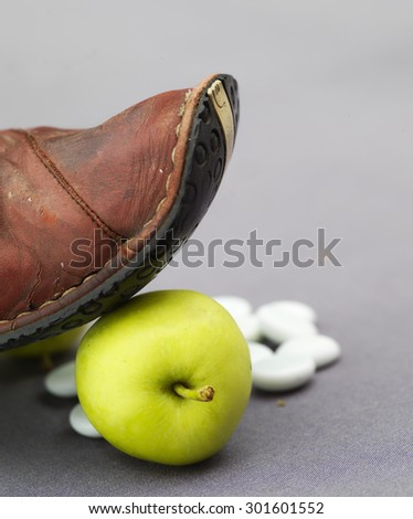 Side shot of a red shoe on ripe yellow apple, studio square shot - stock photo
