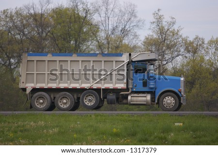Side Shot of Dumptruck on the highway - stock photo