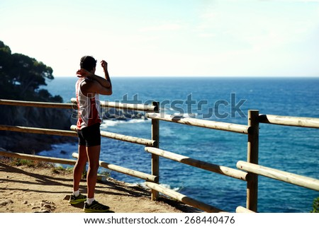 Side shot of handsome young runner stretching before starting his run while standing on edge of a cliff with a wooden fence and enjoying ocean view from altitude, cross process, filtered image - stock photo