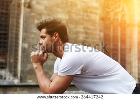 Side shot portrait of handsome man resting chin on clasped hands, confident man thinking about his choice, pensive man standing against gothic building, flare sun light, filtered image - stock photo