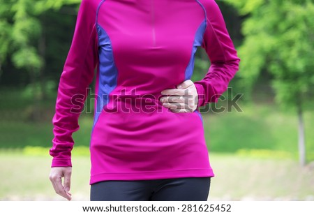 Side stitch - woman runner side cramps after running. Jogging woman with stomach side pain after jogging work out.  - stock photo