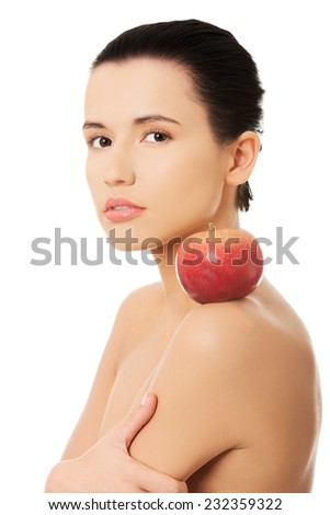 Side view bare brunette with red apple on shoulder.
