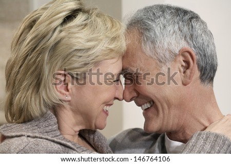 Side view closeup of romantic middle aged couple with heads together - stock photo