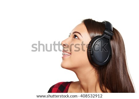Side view closeup portrait of smiling young female listening enjoying music in headphones and looking up at blank copy space, over white background - stock photo