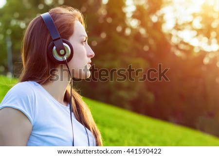 Side view closeup portrait of young attractive girl listen to music with a smart phone in the city park. Blurred background with copy space area for a text. - stock photo