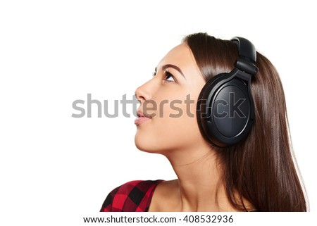 Side view closeup portrait of young female listening enjoying music in headphones and looking up at blank copy space, over white background - stock photo