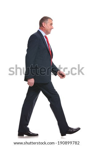side view full length photo of a mid aged business man walking forward and looking away. isolated on a white background - stock photo