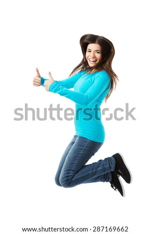 Side view happy woman jumping with thumbs up. - stock photo