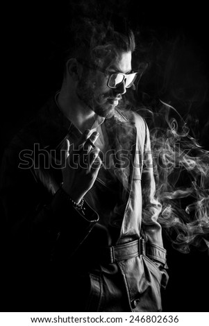 Side view image of a casual young man wearing a leather coat. He is looking down while smoking a cigarette. - stock photo