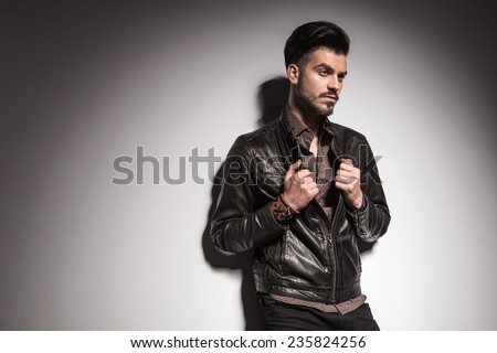 Side view image of a handsome young fashion man fixing his jacket while looking away from the camera. - stock photo