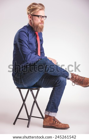 Side view image of a young casual man sitting on a stool holding his legs crossed while looking away from the camera, thinking. - stock photo