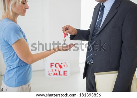 Side view mid section of a real estate agent passing house key to woman - stock photo
