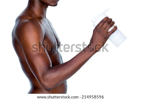 Side view mid section of a sporty young man holding protein drink over white background