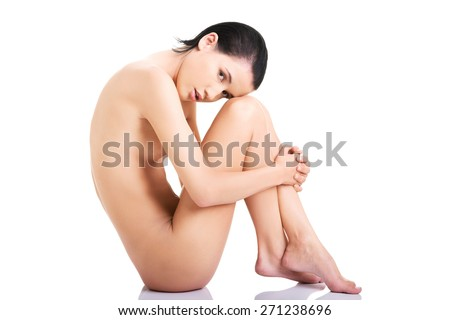 Side view nude woman with knees close to the chest.
