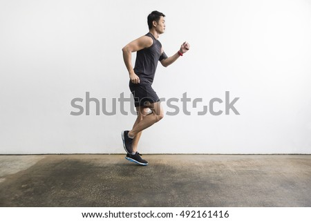 Side view of a Athletic Asian man running outdoors training for marathon. Athletic Asian fitness concept.