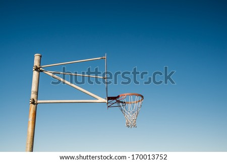 Side view of a basketball hoop against blue sky - stock photo