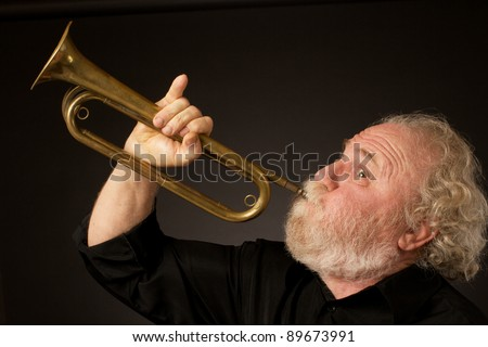 Side view of a bearded senior musician blowing a bugle, held with an expressively raised little finger. Black background, horizontal format and copy space. - stock photo