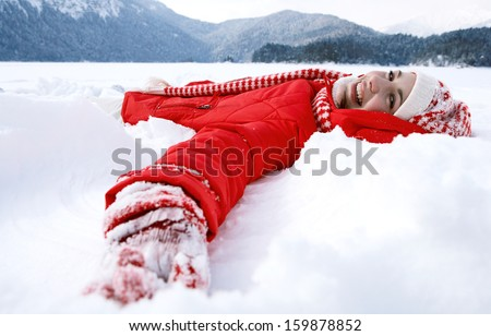 Side view of a beautiful young woman laying down on a frozen snow lake moving her arms up and down creating an angel figure shape, playing games during a sunny winter  vacation. - stock photo