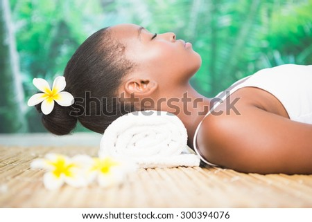 Side view of a beautiful young woman on massage table at spa center - stock photo