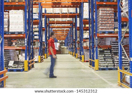 Side view of a blurred man walking through warehouse