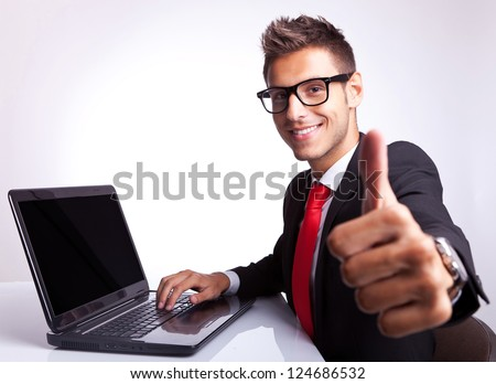 side view of a business man working on laptop and making the ok gesture - stock photo