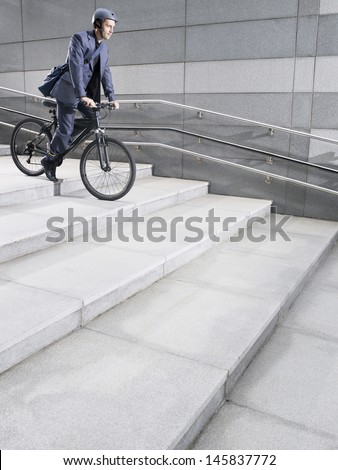 Side view of a businessman in crash helmet riding bicycle down steps - stock photo