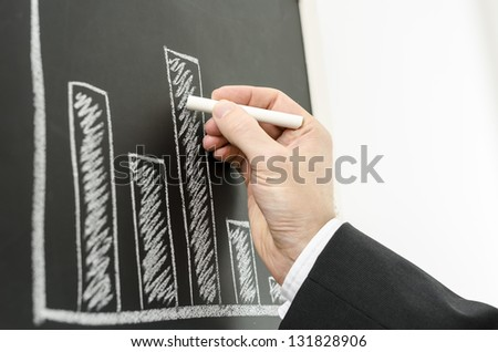 Side view of a businessman's hand drawing business graph with a chalk on a black board. - stock photo