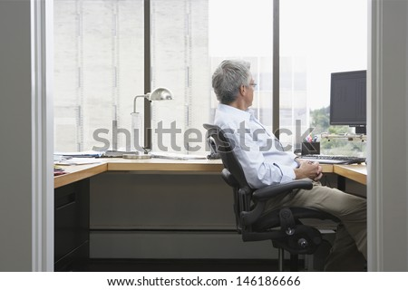 Side view of a businessman sitting at desk in office - stock photo