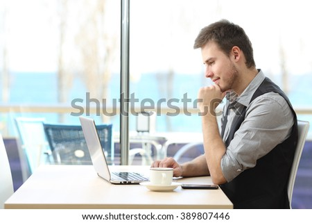 Side view of a businessman using a laptop on line sitting in a bar with a window and the sea in the background - stock photo