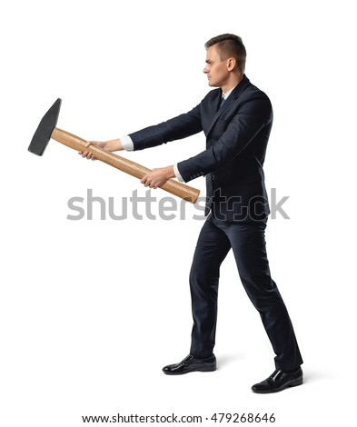 Side view of a businessman with big hammer in his arms destroying something, isolated on white background. Inner and physical strength. Business staff. Hard work.