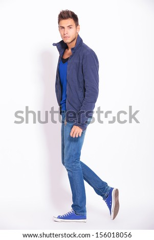 side view of a casual man in jeans and jacket posing and looking at the camera