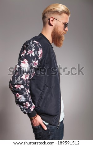 side view of a casual young man with a long red beard holding his hands in his back pockets and looking forward, away from the camera. on gray studio background - stock photo