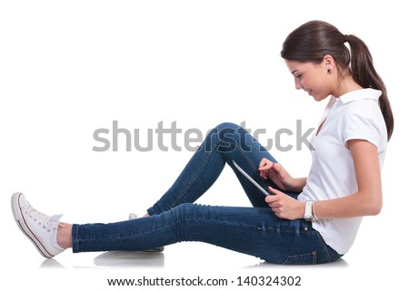 side view of a casual young woman layed on the floor and playing on her tablet. isolated on white background - stock photo