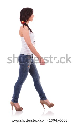 side view of a casual young woman walking ahead and looking away. on white background - stock photo