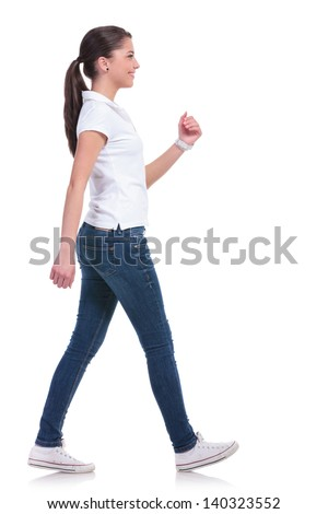side view of a casual young woman walking away from the camera and smiling. isolated on white background - stock photo
