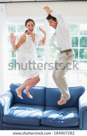 Side view of a cheerful young couple jumping on couch at home - stock photo