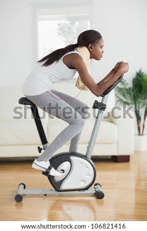 Side view of a concentrated black woman doing exercise bike in a living room - stock photo