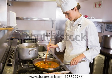 Side view of a concentrated female cook preparing food in the kitchen - stock photo