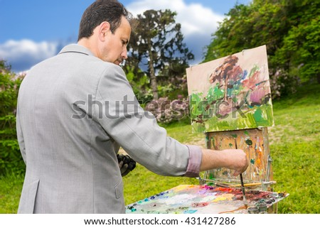 Side view of a concentrated male artist working  on a trestle and easel painting with oils and acrylics during an art class in a garden - stock photo