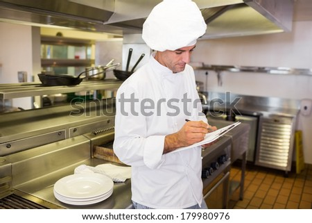 Side view of a concentrated male cook writing on clipboard in the kitchen