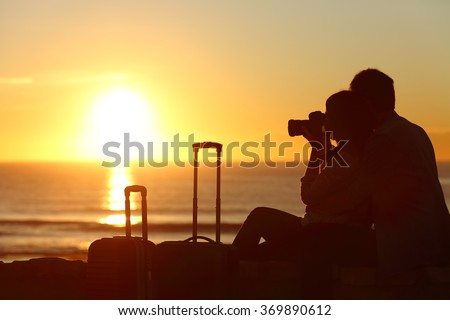 Side view of a couple silhouette of tourists photographing the sun at sunset on the beach on holidays - stock photo