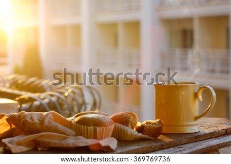 Side view of a cup of coffee and Banana Muffin in a brown baking paper cup on wood with morning light. - stock photo