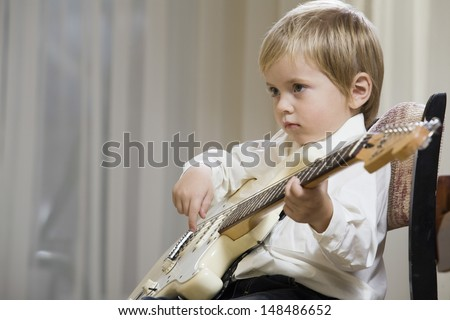 Side view of a cute little boy playing guitar - stock photo