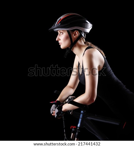 side view of a cyclist girl on black background - stock photo