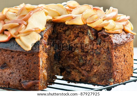Side view of a delicious homemade apple cake with pecan nuts and cinnamon. - stock photo