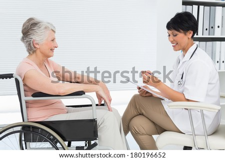 Side view of a doctor talking to a senior patient in wheelchair at the hospital - stock photo