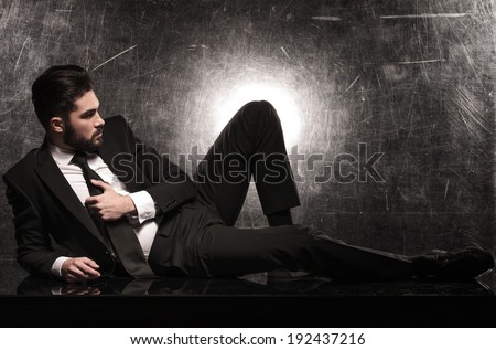side view of a dramatic business man on the floor looking away from the camera - stock photo