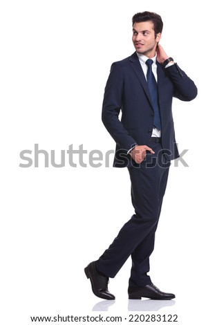 Side view of a elegant business man walking on white background with one hand in his pocket and the other one to his neck, looking away from the camera - stock photo
