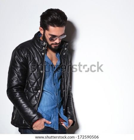 side view of a fashion man in leather jacket looking down in studio - stock photo