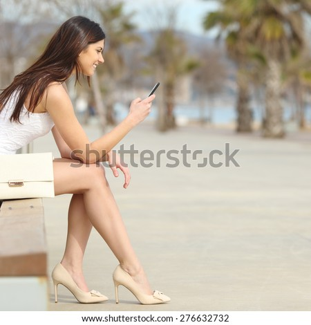 Side view of a fashion woman using a smartphone sitting on a bench in the street - stock photo